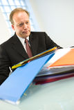 Man with pile of paperwork. Businessman with pile of paperwork stacked on a desk in a white room Stock Photos
