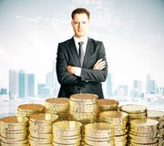 Man with piles of coins at city background Stock Photo