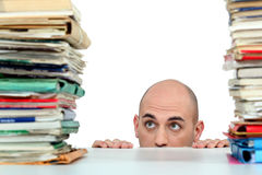 Man with piles of folders. Man staring nervously at piles of folders Royalty Free Stock Image