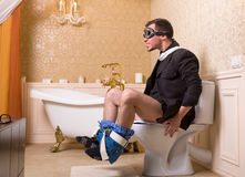 Man in pilot glasses sitting on the toilet bowl Stock Photos