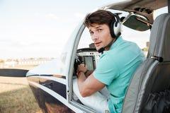 Man pilot- sammanträde i kabin av det lilla flygplanet Arkivfoto