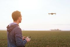 Man piloting drone at sunset stock photo