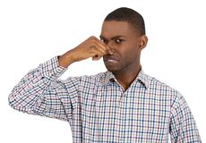 Man pinches his nose with disgust as something stinks Stock Image
