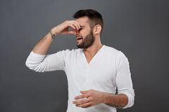 Man pinches nose because of bad smell over grey background. Young handsome man pinches his nose because of bad smell over grey background. Copy space royalty free stock photography