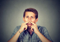 Man pinches nose looks with disgust something stinks bad smell. Man pinches nose with fingers looks with disgust something stinks bad smell on gray background royalty free stock image