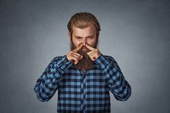 Man pinches nose looks with disgust something stinks bad smell stock photography