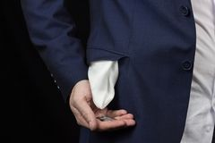 A man in a pingback turns his pocket inside out and holds a coin in his hand, a close-up royalty free stock images