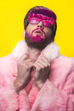 Man in a Pink Fur Coat and Carnival Glasses. Portrait of glamour man with red beard. Guy in a pink fur coat and funny  sunglasses Stock Photo