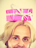 Man with pink gift box on his head. Celebration and giving concept. Young man with pink gift box on his head. Guy have idea for present Royalty Free Stock Photos