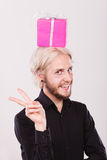 Man with pink gift box on his head. Celebration and happiness concept. Cool happy young man with pink gift box on his head. Guy have crazy idea for present Stock Photography