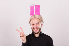Man with pink gift box on his head. Celebration and happiness concept. Cool happy young man with pink gift box on his head. Guy have crazy idea for present Stock Images