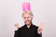 Man with pink gift box on his head. Celebration and happiness concept. Cool happy young man with pink gift box on his head. Guy have crazy idea for present Stock Photos