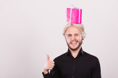 Man with pink gift box on his head. Celebration and happiness concept. Cool happy young man with pink gift box on his head. Guy have crazy idea for present Stock Image