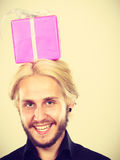 Man with pink gift box on his head. Celebration and happiness concept. Cool happy young man with pink gift box on his head. Guy have crazy idea for present Stock Photo