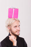 Man with pink gift box on his head. Celebration and happiness concept. Stylish smiling young man with pink gift box on his head. Guy have idea for present Royalty Free Stock Photography