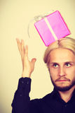 Man with pink gift box on his head. Confused man with pink gift box on his head Stock Photo