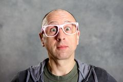 Man with pink glasses looking amazed in to the camera. Young man with pink glasses looking amazed in to the camera Royalty Free Stock Images
