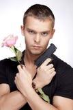 Man with pink rose and gun stock image