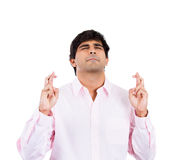 Man with pink shirt crossing fingers, wishing and dreaming for something Royalty Free Stock Image