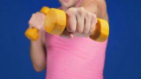 A man in a pink T-shirt with a deep neckline is boxing dumbbells. focus on dumbbells, body blurry. copy space royalty free stock photo
