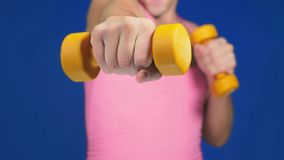 A man in a pink T-shirt with a deep neckline is boxing dumbbells. focus on dumbbells, body blurry. copy space royalty free stock images