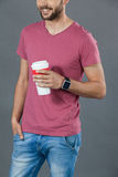 Man in pink t-shirt holding a disposable coffee cup. Mid section of man in pink t-shirt holding a disposable coffee cup against grey background Royalty Free Stock Photos