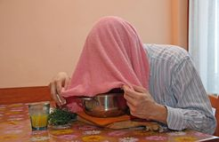 Man with pink towel breathe balsam vapors to treat colds and flu royalty free stock photos