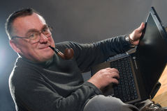 Man with pipe and laptop Royalty Free Stock Photography