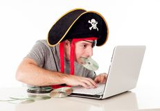 Man in pirate hat downloading music on a laptop. Man dressed as a pirate with a CD in his mouth on his computer downloading music and movies on a white stock photos