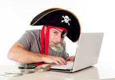 Man in pirate hat downloading music on a laptop. Man dressed as a pirate with a CD in his mouth on his computer downloading music and movies on a white royalty free stock image