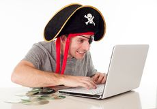 Man in pirate hat downloading music on a laptop. Man dressed as a pirate on his computer downloading music and movies on a white background royalty free stock photos