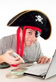 Man in pirate hat downloading music on a laptop Stock Photography