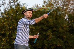 Man in pirate suit is blowing soap bubbles. Royalty Free Stock Photography