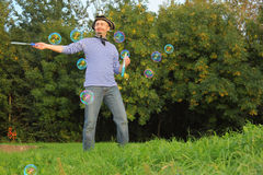 Man in pirate suit is blowing soap bubbles. Stock Image