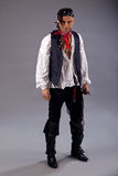 Man pirates of the caribbean. Man dressed in pirates of the caribbean style with bandana, white shirt sword, whip, white shirt, black trousers and boots on a Stock Photo