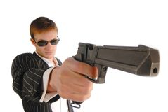 Man with pistol. Young man in black suit with a pistol in hand, close up royalty free stock image