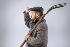 Man with pitchfork on his shoulder gives greeting gesture, dressed in old-fashioned clothes - cap and wool-padded jacket - Telogre. Ika. Idea - life in the royalty free stock image