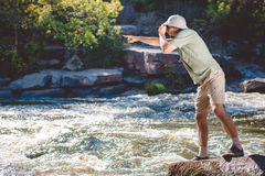 Man in pith helmet standing on rocky riverbank Royalty Free Stock Photo