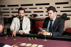 Man placing bet on a poker game. Good looking Latin men in a suit placing a bet during a poker game at a casino Royalty Free Stock Photography