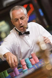 Man placing bet at roulette table Stock Photos
