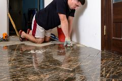 Man placing ceramic floor tile in position over adhesive stock image