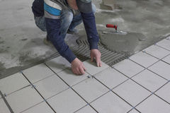 Man placing ceramic floor tile in position over adhesive Stock Photos