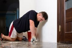 Man placing ceramic floor tile in position over adhesive. 2018 Stock Photos