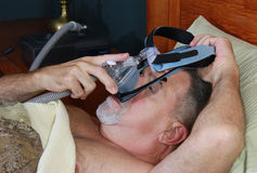 Man Placing CPAP Headgear. A man places a CPAP (continuous positive airway pressure) mask and headgear over his head Stock Photos