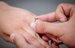 Man placing a diamond engagement ring on finger of his fiance Royalty Free Stock Photo