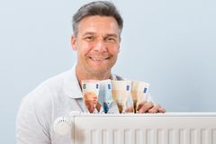 Man placing euro notes on radiator Royalty Free Stock Images