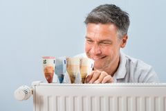Man placing euro notes on radiator Stock Photos