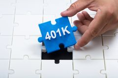Man placing final 401k piece into jigsaw puzzle. Close-up of a man`s hand placing final blue 401k piece into jigsaw puzzle royalty free stock images