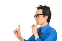 Man placing finger on lips pointing to say shhh be quiet. Closeup side view profile portrait young man placing finger on lips pointing to say shhh be quiet Royalty Free Stock Photo