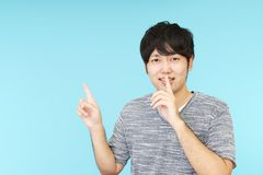Man placing finger on lips. Portrait of a man making silence gesture stock photography